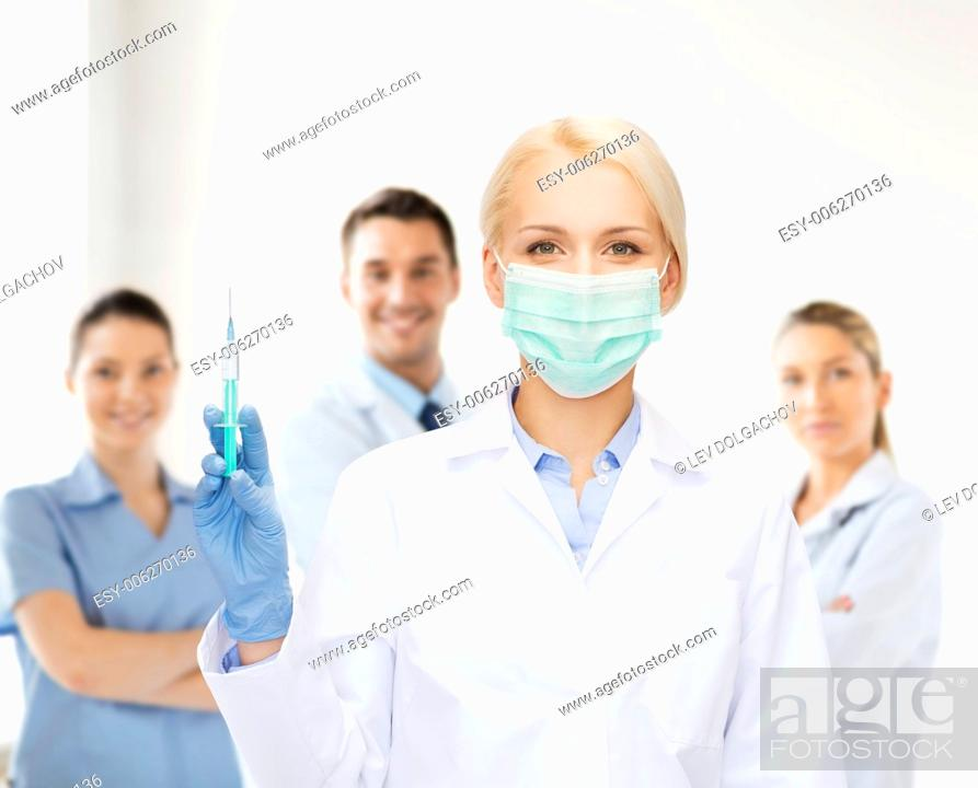 Stock Photo: healthcare and medicine concept - female doctor in mask holding syringe with injection.
