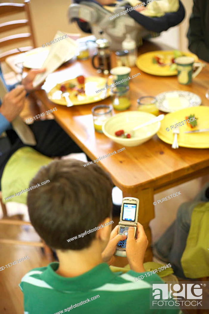 Stock Photo: High angle view of a boy sitting at a dining table and using a mobile phone.