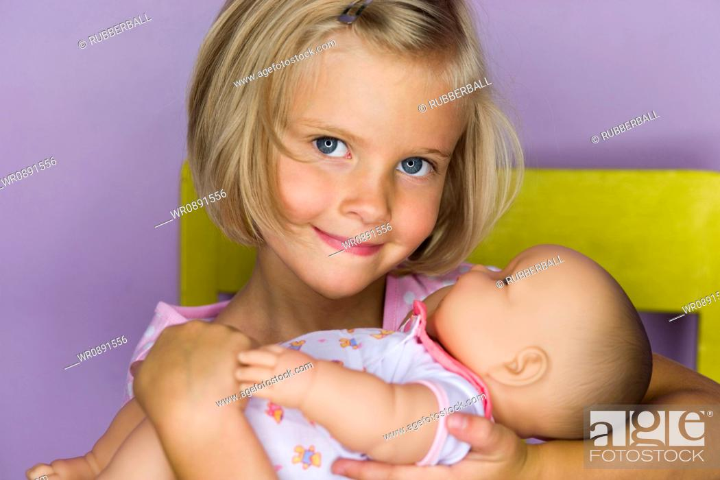 Stock Photo: Portrait of a girl holding a doll.