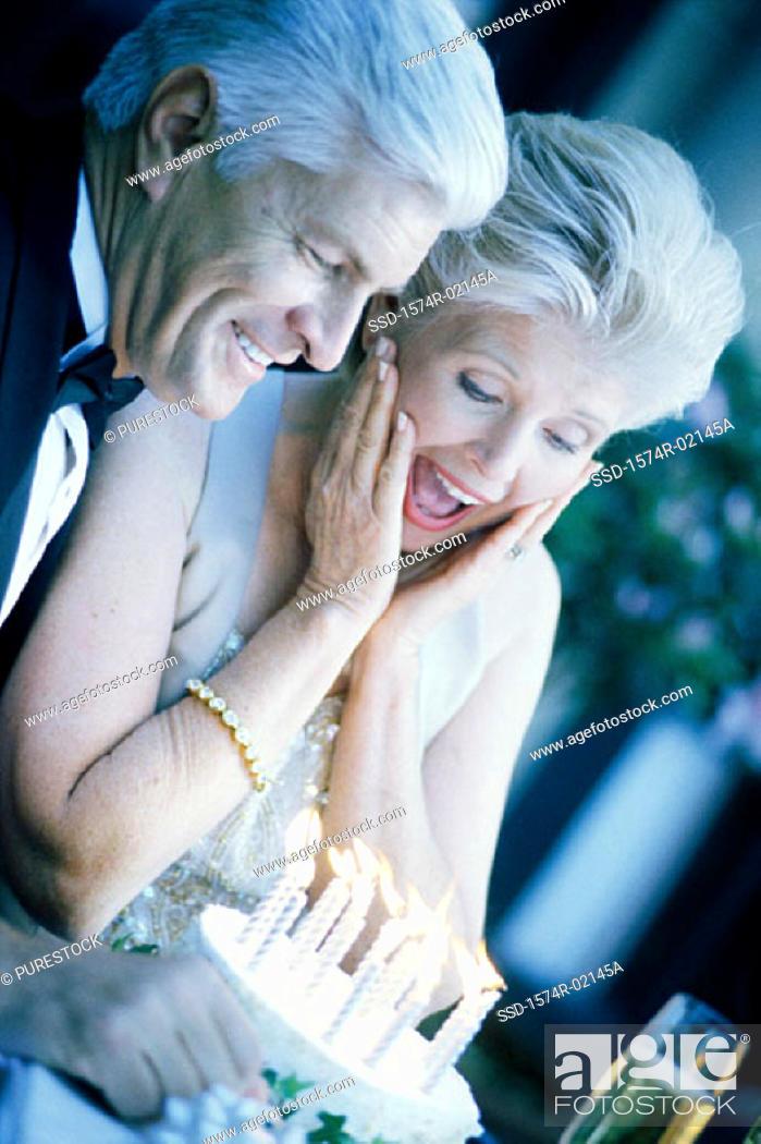Stock Photo: Senior couple with a birthday cake.
