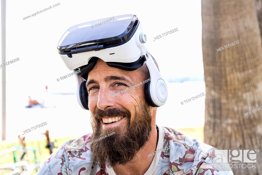 Stock Photo: Smiling mature man with virtual reality glasses.