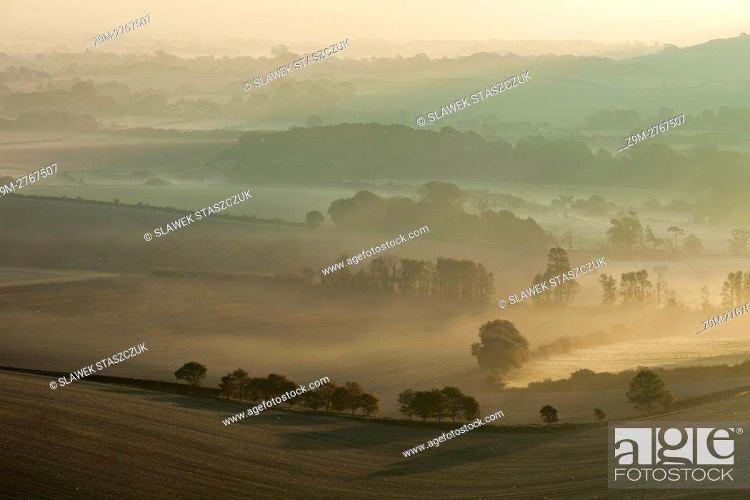 Stock Photo: Misty autumn sunrise in South Downs National Park near Alfriston, East Sussex, England.
