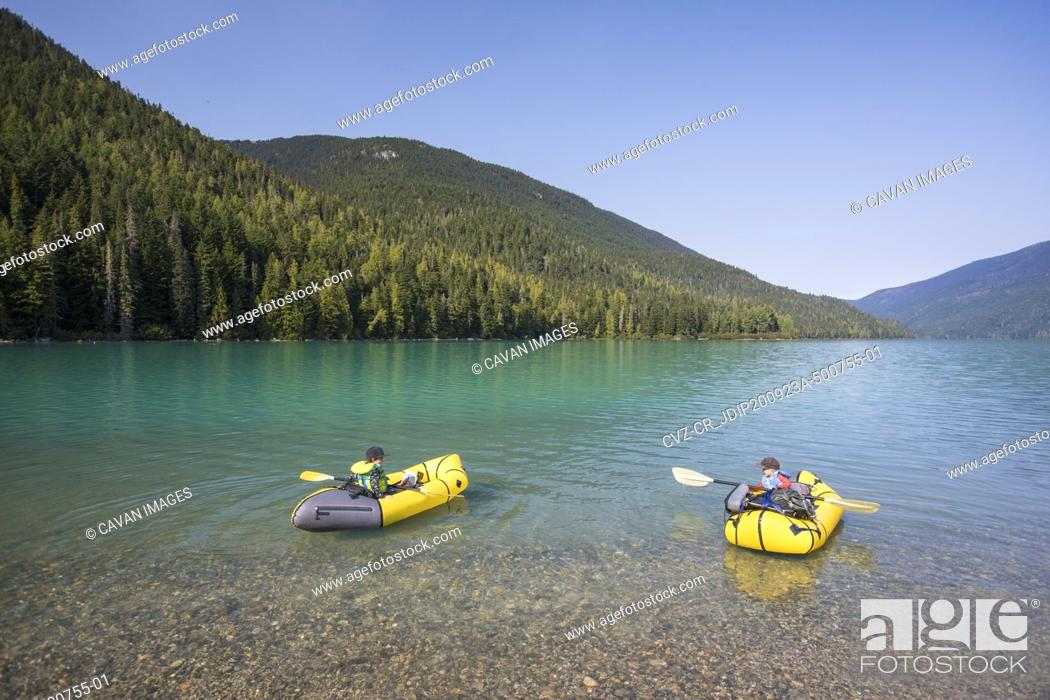 Photo de stock: Two young boys learning how to paddle kayak on scenic lake.