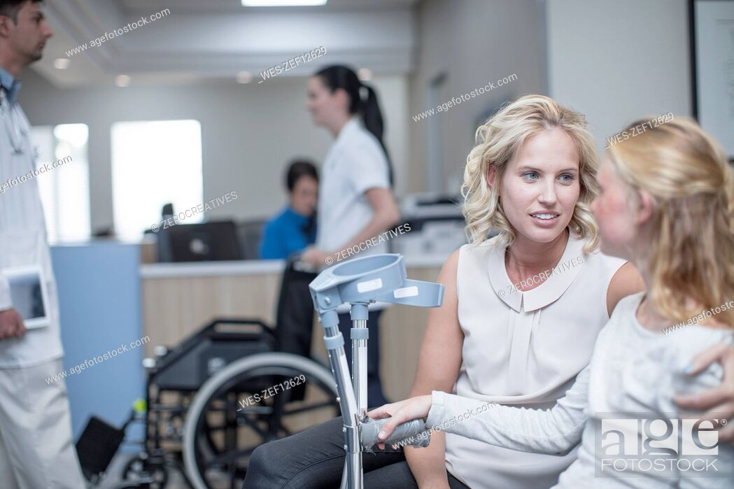 Stock Photo: Girl with crutches sitting with her mother in reception area.