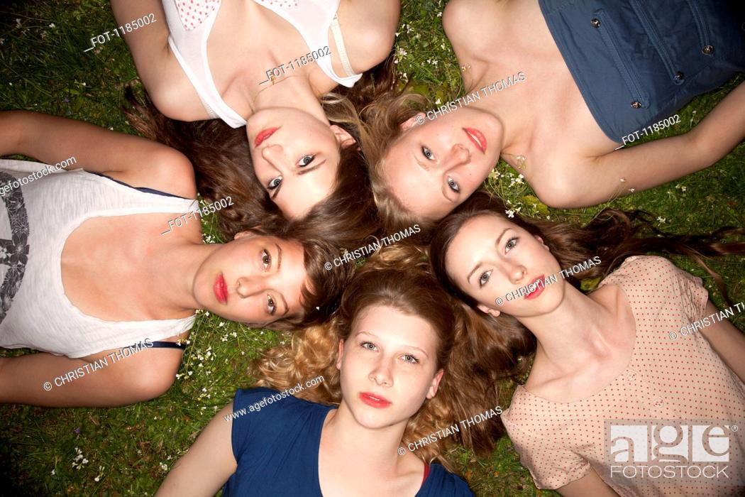 Stock Photo: Five female friends lying in the grass in a circle looking sensually at the camera.