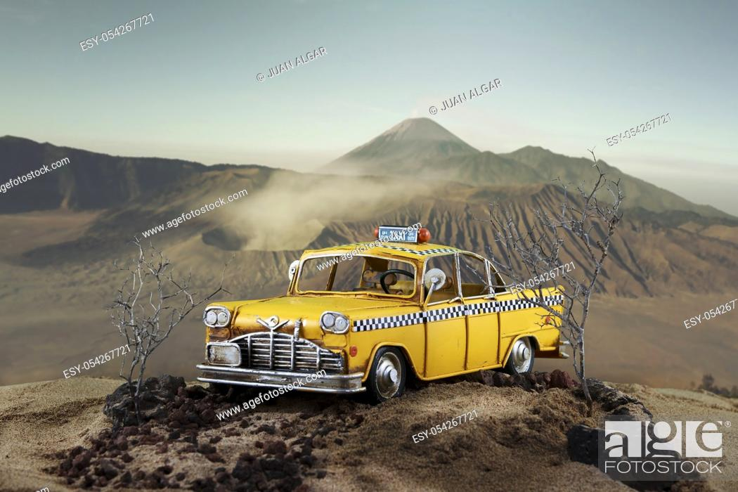 Stock Photo: An old yellow taxi car parked on the background of the picturesque hill. Horizontal outdoors shot.