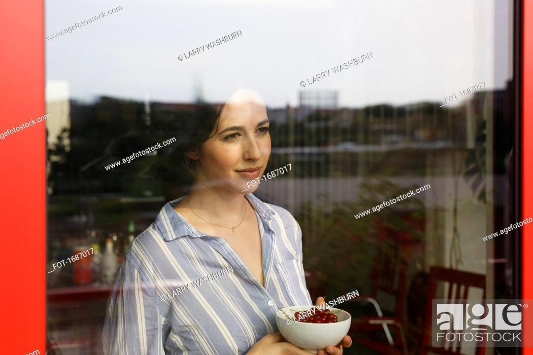 Stock Photo: Thoughtful young woman holding bowl with red currants while looking through window.