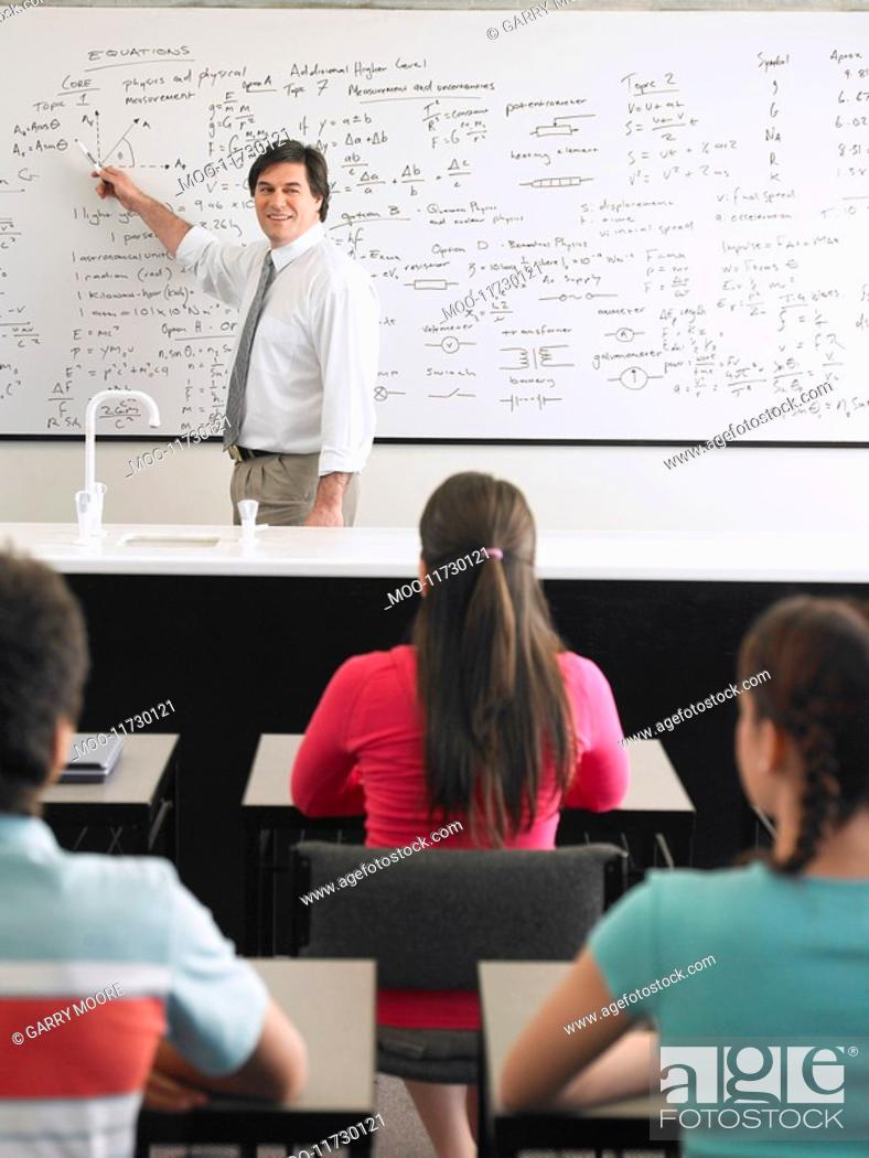 Stock Photo: Students sitting in classroom listening to teacher at whiteboard.