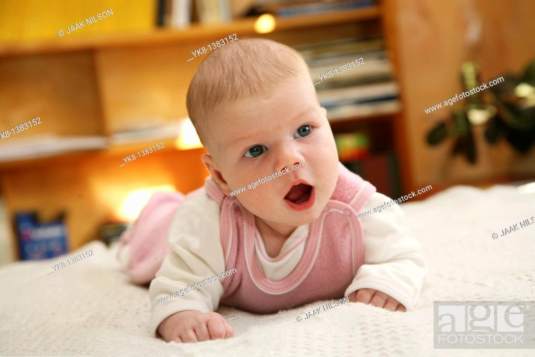 Stock Photo: One month and two weeks old infant on bed.