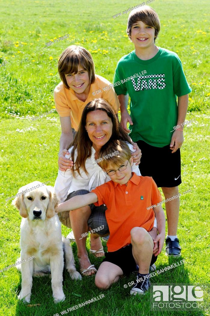 Stock Photo: Mother with her three sons and a dog.