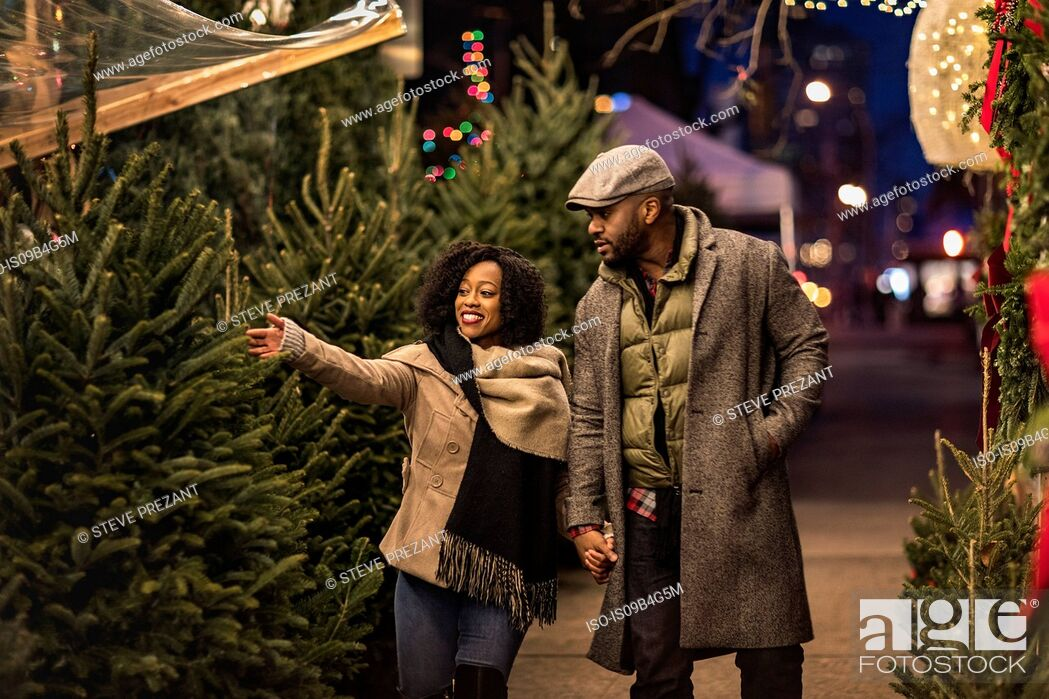 Stock Photo: Couple selecting Christmas tree at Christmas market at night, New York, USA.