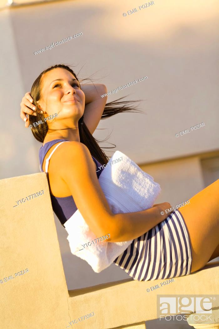 Stock Photo: Pretty young woman is holding hair after a strong wind.
