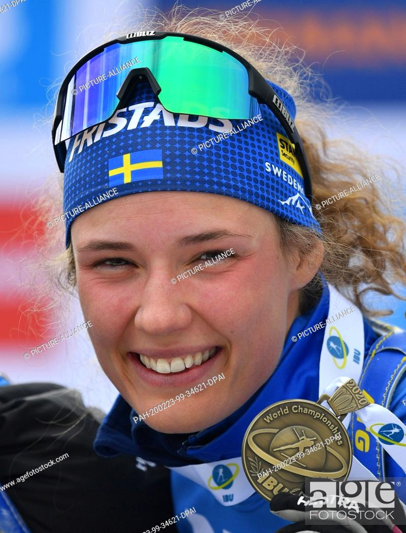 Stock Photo: 23 February 2020, Italy, Antholz: Biathlon: World Championship, mass start 12.5 km, women. Hanna Oeberg from Sweden shows her bronze medal after her third place.