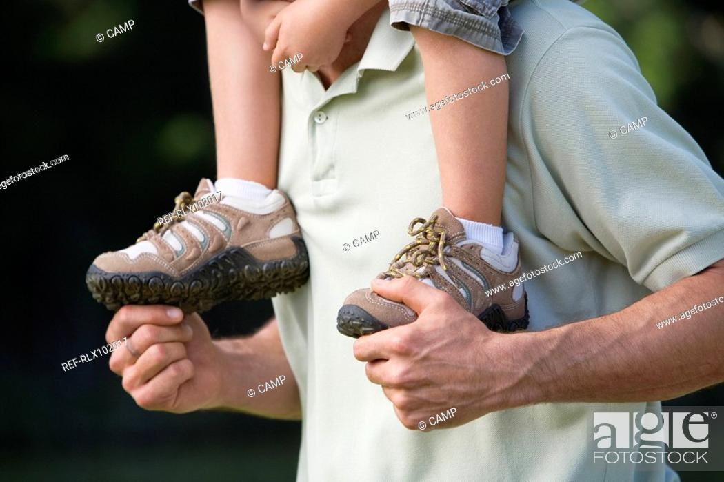 Stock Photo: Father carrying son 4-7 on his shoulders, outdoors, close-up, detail.