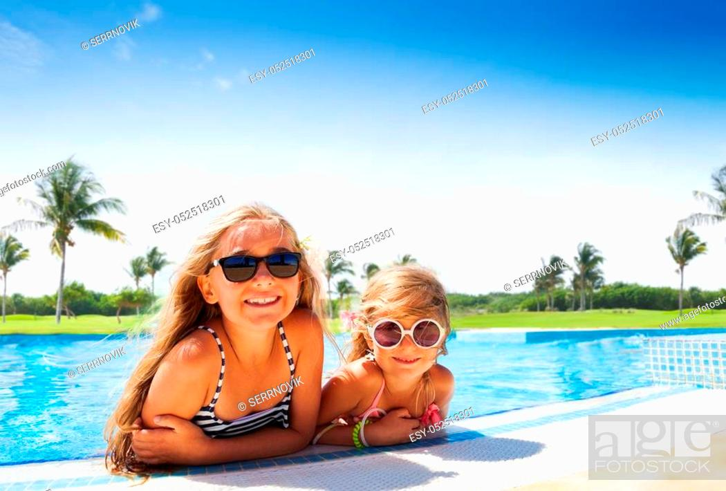 Stock Photo: Portrait of two age-diverse girls, happy friends in swimsuits and sunglasses, enjoying summer vacation, relaxing in the swimming pool.