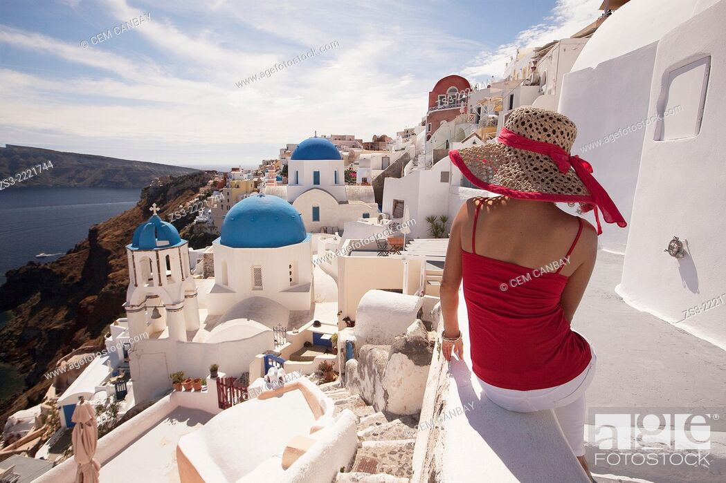 Stock Photo: Woman in front of the blue domed church in Oia town looking at Caldera, Santorini, Cyclades Islands, Greek Islands, Greece, Europe.