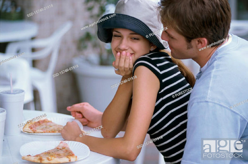 Stock Photo: Young couple sitting at a table outdoors.