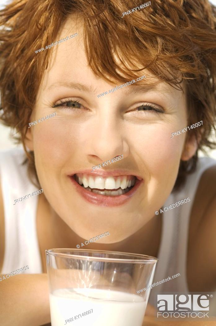 Stock Photo: Portrait of a young smiling woman, glass of milk.