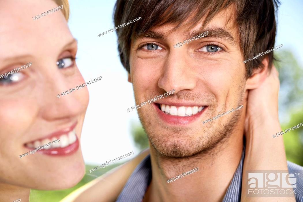 Stock Photo: Germany, Cologne, Young couple embracing, smiling, portrait.