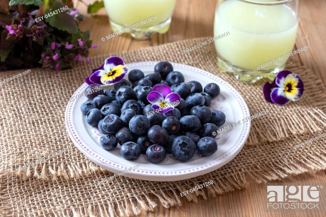Stock Photo: Blueberries on a plate, with fresh whey in the background.