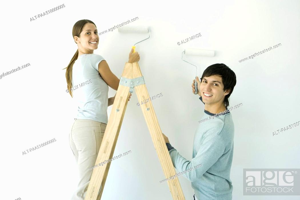 Stock Photo: Couple painting wall with rollers, both smiling over their shoulder at camera.