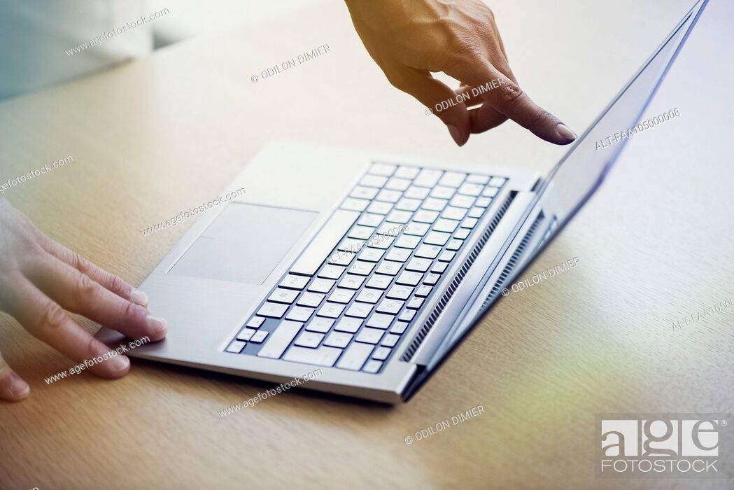 Stock Photo: Salesperson showing laptop computer to shopper.