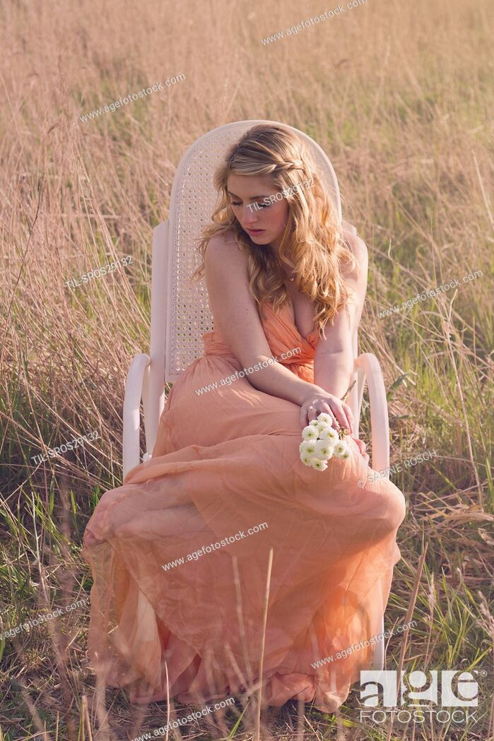 Imagen: Young women sitting in a rocket chair in the sun wearing a pastel colored summer dress with white flowers in her hands.