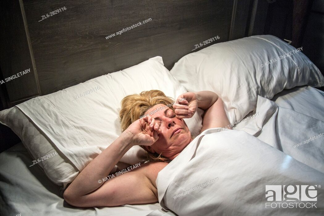 Stock Photo: Caucasian female. slepping, streching and waking up in bed.
