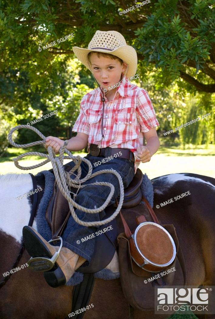 Stock Photo: A boy riding a horse and holding a lasso.