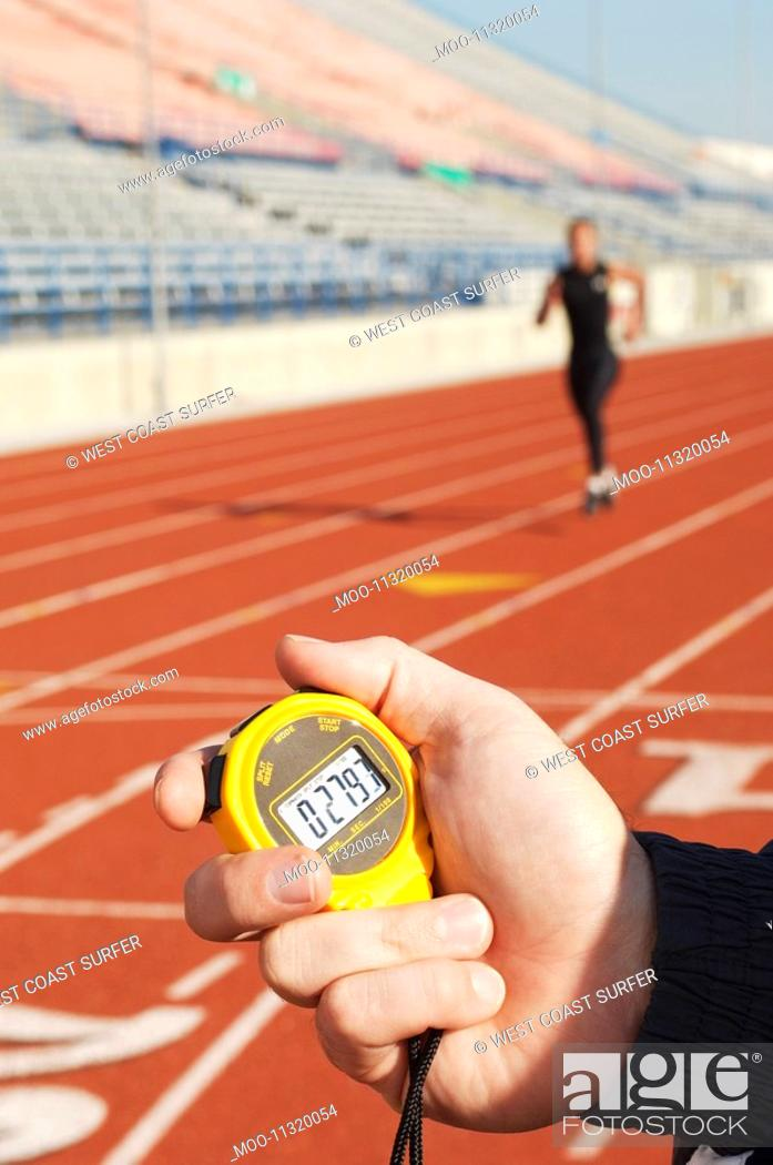 Stock Photo: Man holding stopwatch close up of hand timing runner on running track.
