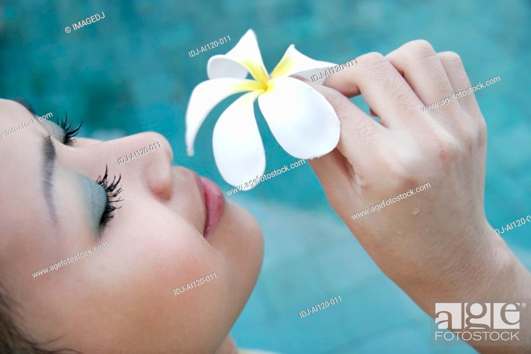 Stock Photo: A teenage girl holding a flower.