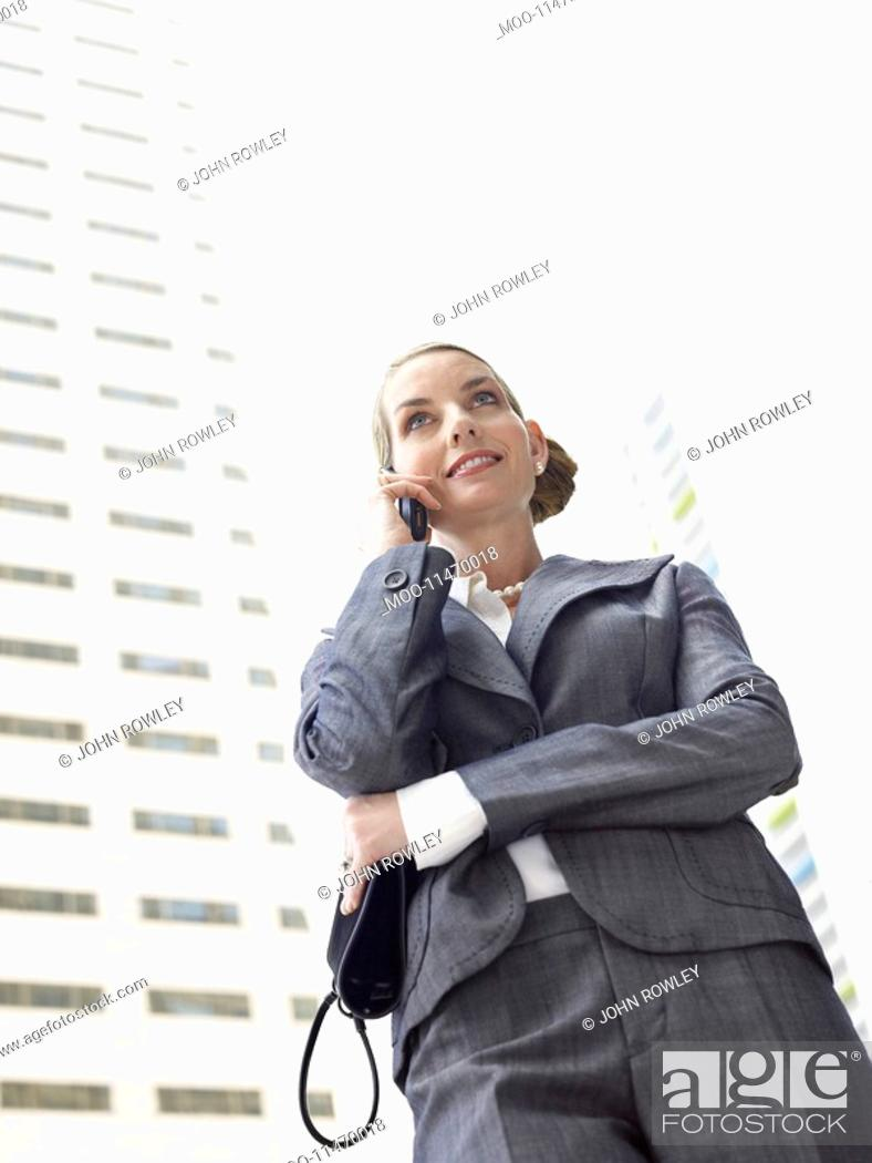 Stock Photo: Businesswoman using mobile phone outdoors.