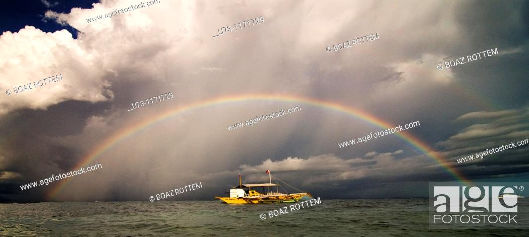Stock Photo: A beautiful full size rainbow on a stormy day in The Philippines.