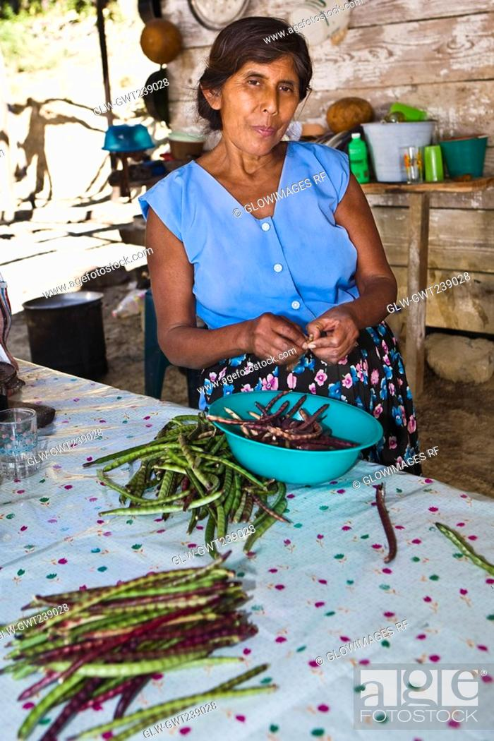 Stock Photo: Mature woman peeling beans in a kitchen, Papantla, Veracruz, Mexico.