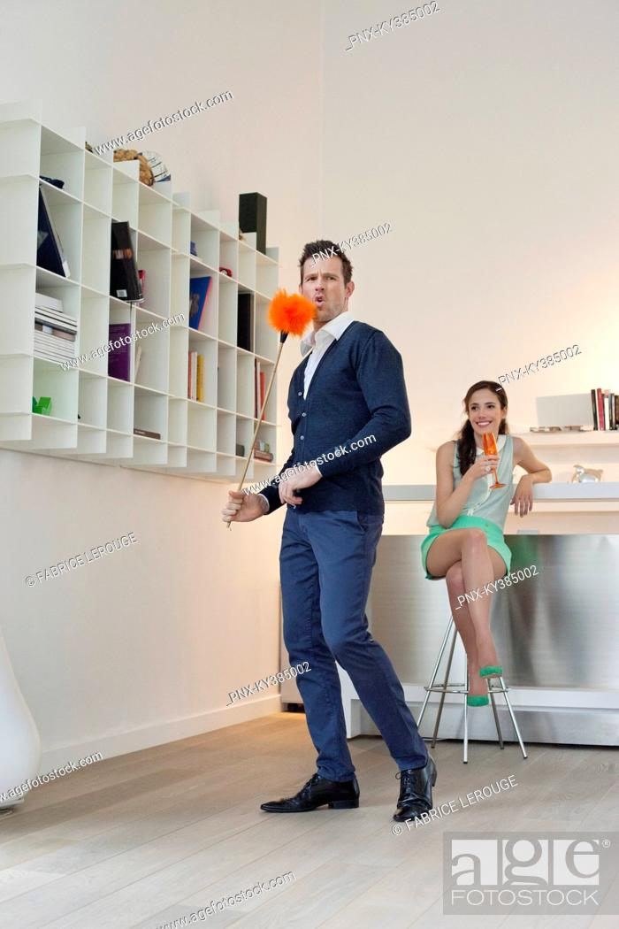 Stock Photo: Man cleaning a bookshelf with his wife drinking champagne in the background.