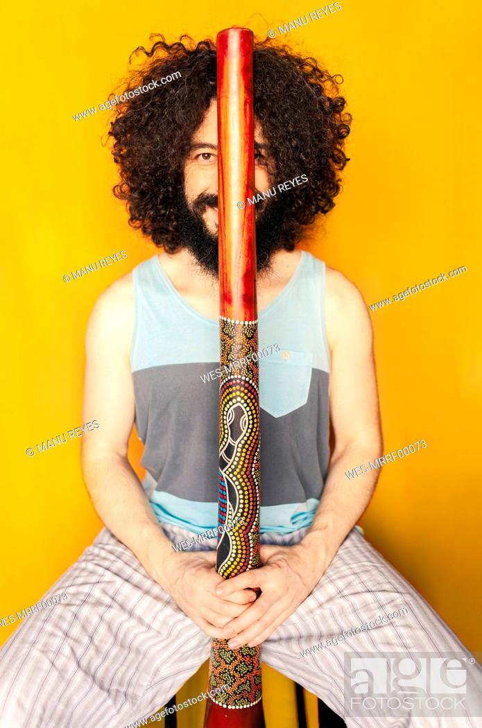 Imagen: Crazy man with curly hair holding didgeridoo while sitting against yellow background.