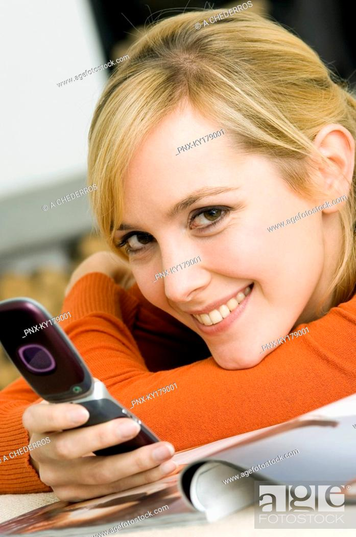 Stock Photo: Portrait of a young woman holding a mobile phone and smiling.
