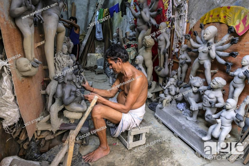 Stock Photo: Kolkata, India - September 2020: A craftsman making clay and straw sculptures for the Durga Puja festival in Kumartuli, the potters' district of northern.
