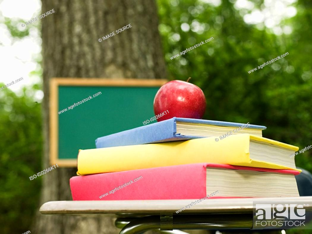 Stock Photo: Books and an apple on top of a desk.