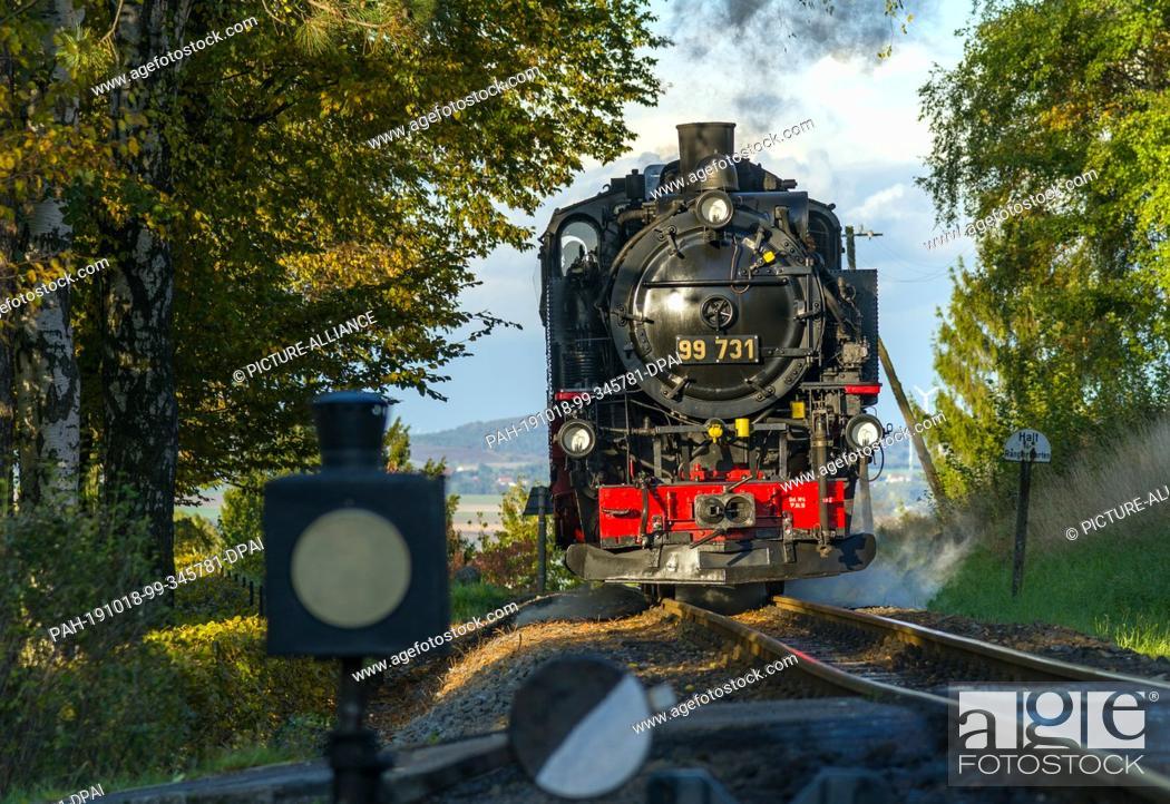 Stock Photo: 10 October 2019, Saxony, Jonsdorf: A steam locomotive of the Zittau narrow-gauge railway runs through the autumn landscape.