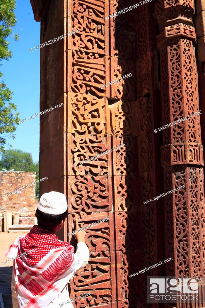 65bca390825e Stock Photo - Muslim boy watching Islamic Ornamentation of Quran inscription  carved on Qutab Minar complex built in 1311 red sandstone tower