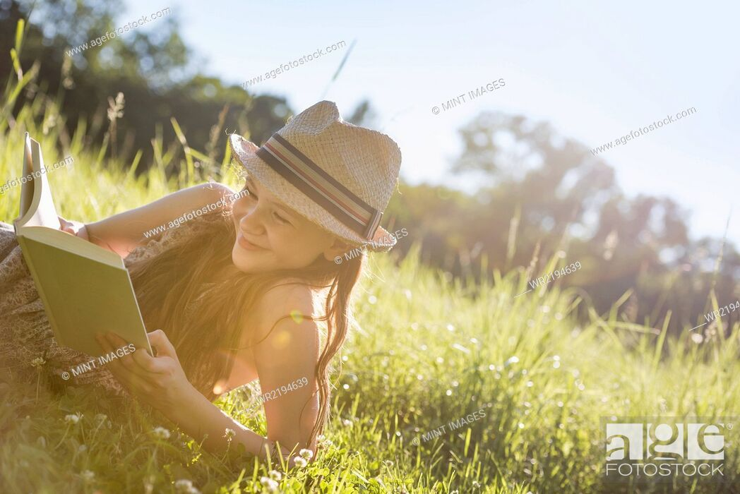 Stock Photo: A young girl in a straw hat lying on the grass reading a book.