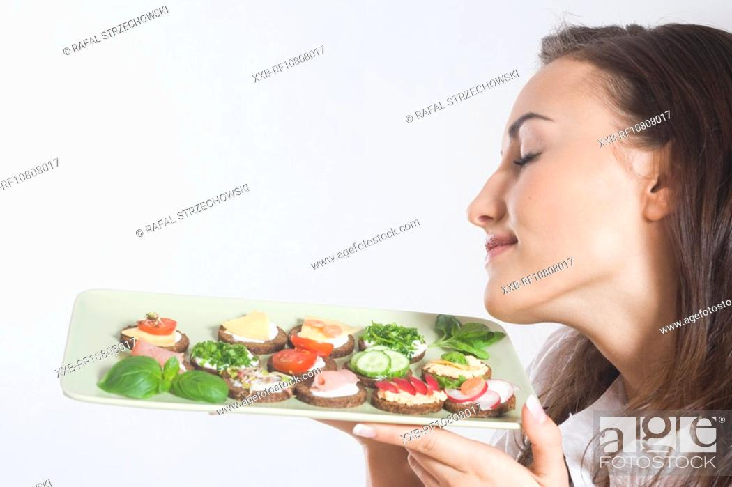 Stock Photo: Young woman holding plate with sandwiches.