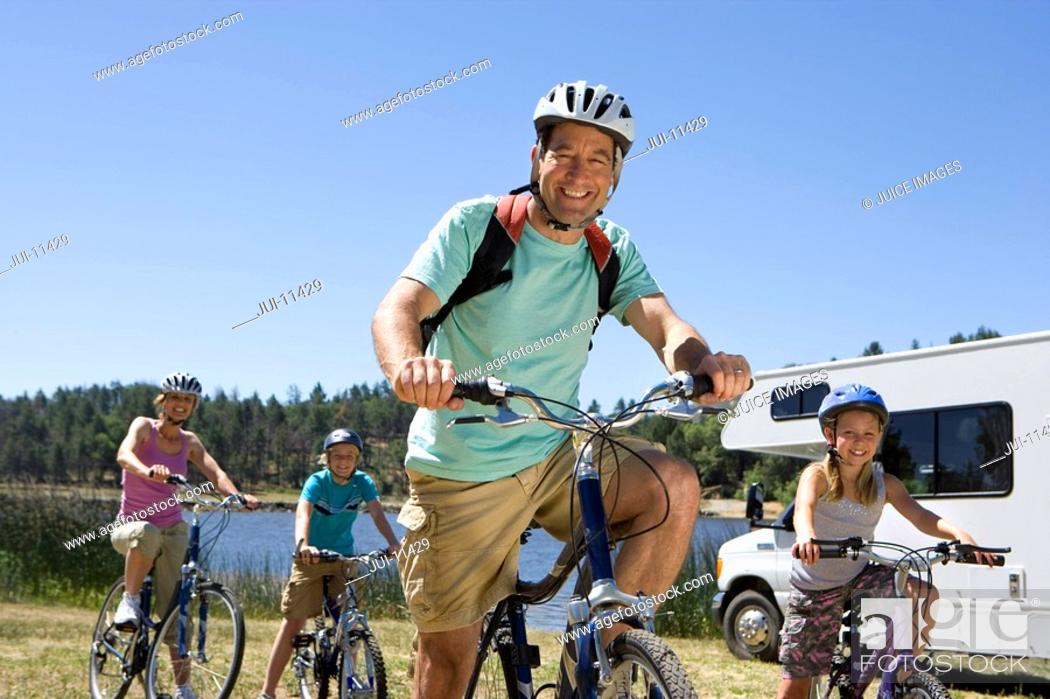 Stock Photo: Family of four on bicycles by motor home, close-up of father, low angle view.
