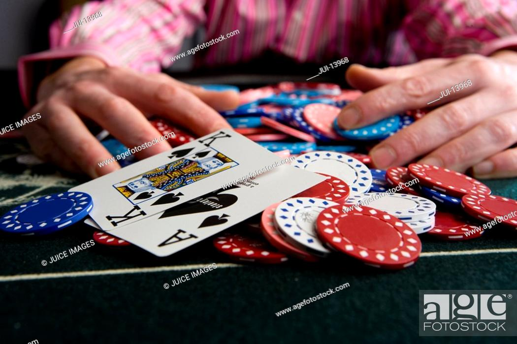 Stock Photo: Man collecting pile of gambling chips on table, close-up of winning cards.