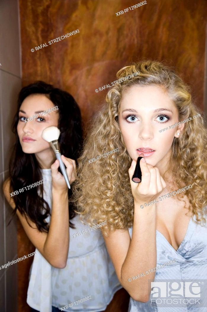 Stock Photo: girls doing makeup in bathroom.