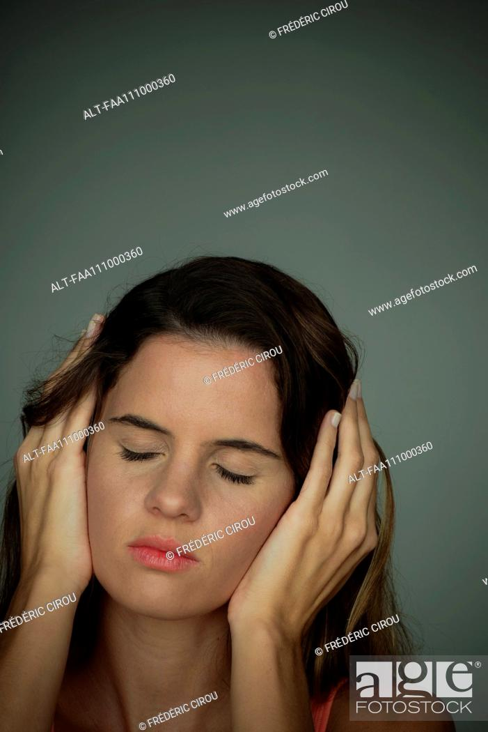 Stock Photo: Woman holding hands over ears with eyes closed.