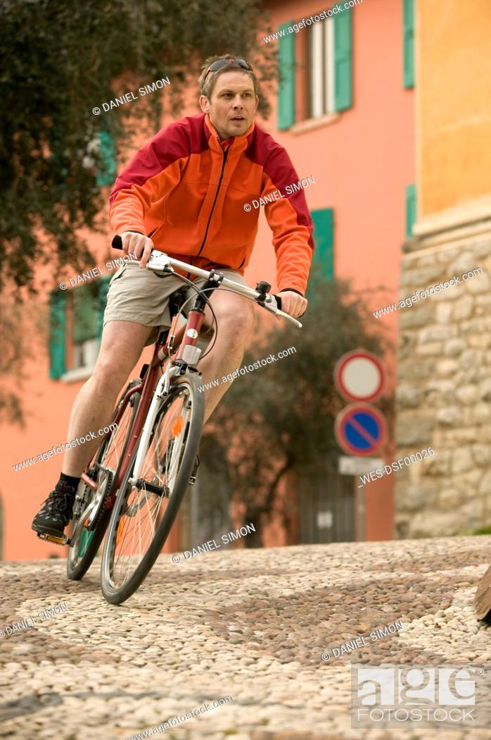 Stock Photo: Italy, Lombardy, Campione, Man mountain biking through village.