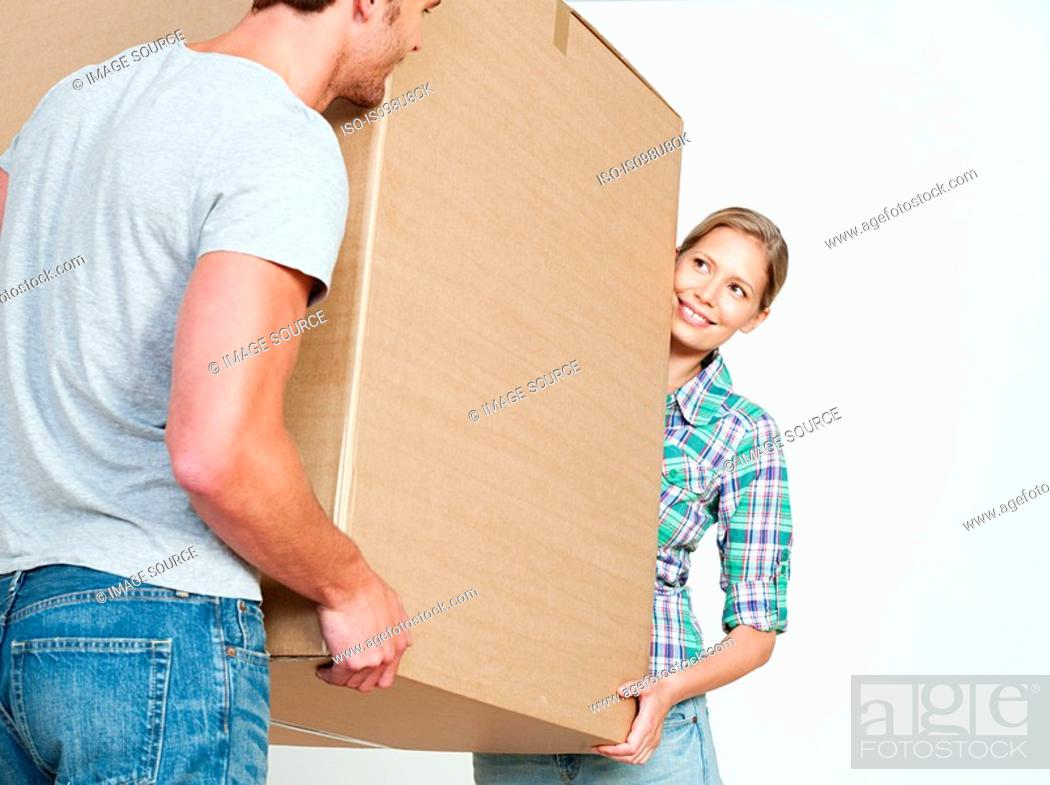 Stock Photo: Young couple carrying cardboard box.