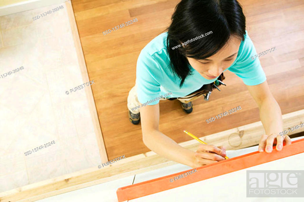 Stock Photo: High angle view of a young woman using spirit level to mark on a wall.
